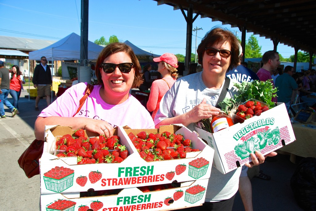 Two Mom's carry home flats of strawberries and a Delvin Farms CSA.